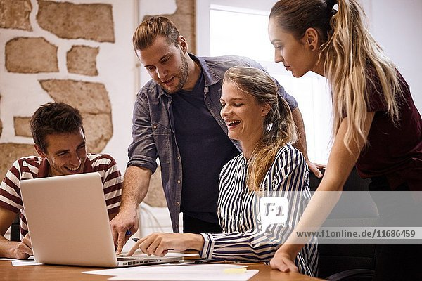 Happy young team laughing while pointing at the laptop they are sharing for their business meeting in an office.