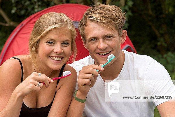 Teenagers Brushing their teeth outside their tent