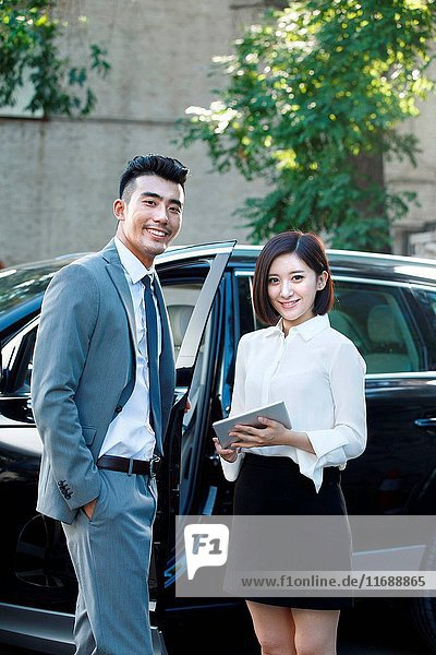 Two business people standing by car