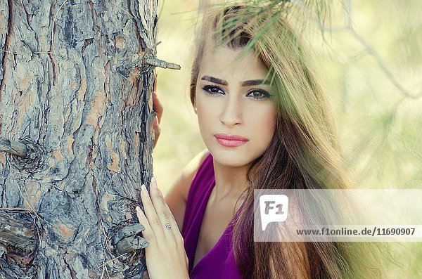 Beautiful young woman leaning against a tree looking away.