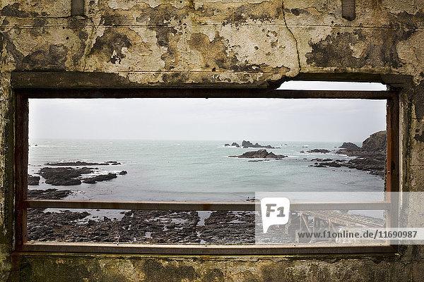 Cornish sea and rocks seen through an old window.