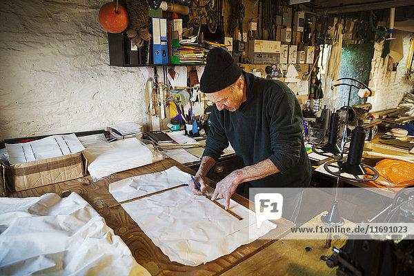Mann in einer Segelmacherwerkstatt  der ein Stück Stoff für ein Segel misst.