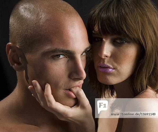 Nacktes Paar  Mann lutscht am Daumen der Frau.