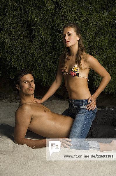 Mann und Frau sitzen an einem Sandstrand.