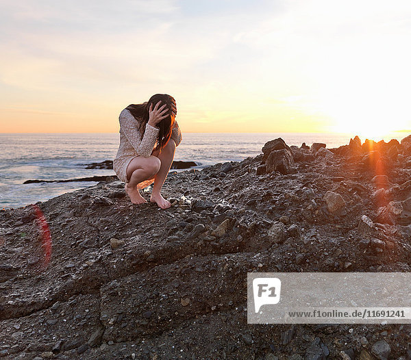 Frau hält ihren Kopf an felsigem Strand