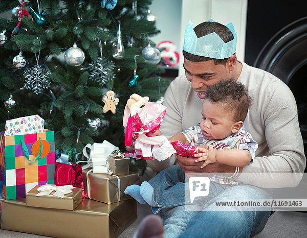 Vater und kleiner Junge öffnen Weihnachtsgeschenke