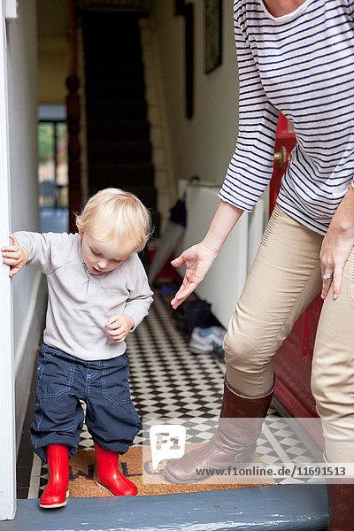 Junge und Mutter treten auf die Türschwelle