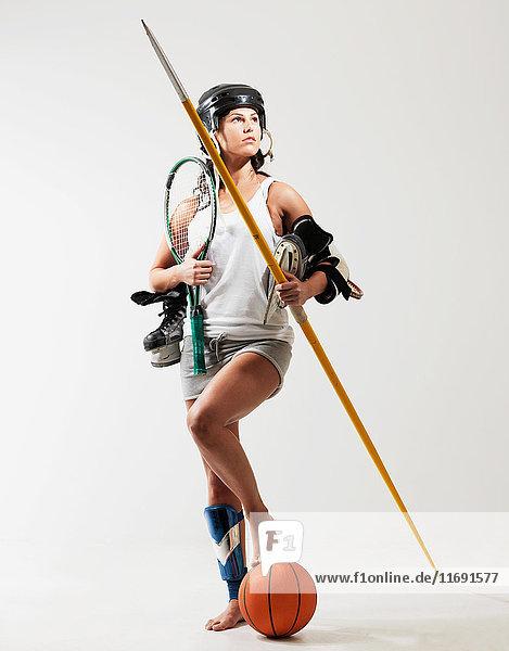 Junge Frau hält Sportgerät vor weissem Hintergrund