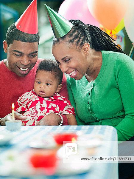 Eltern mit Kleinkind bei der ersten Geburtstagsfeier