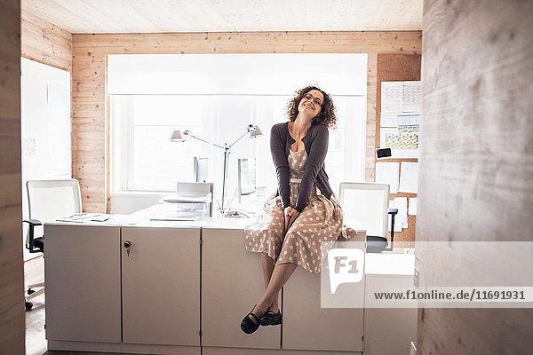 Geschäftsfrau  die im Büro auf dem Schreibtisch sitzt