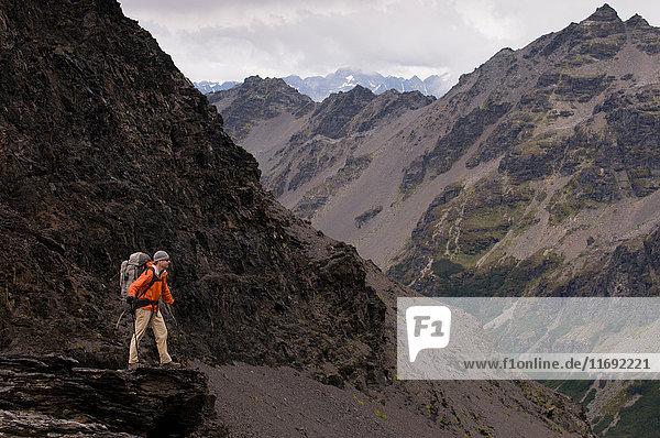 Hiker walking with sticks in rocky hills