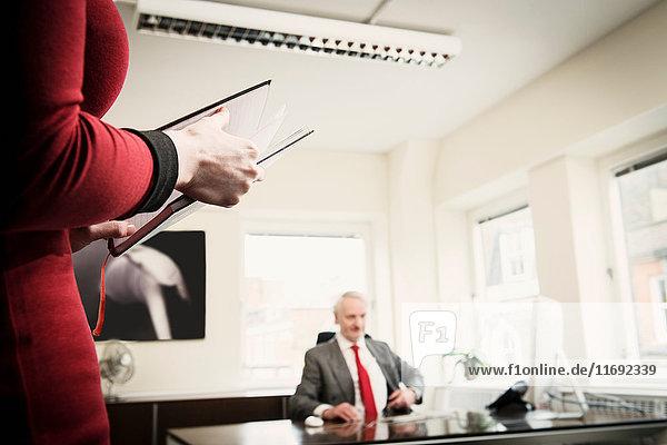 Sekretär hält Tagebuch  Manager sitzt am Schreibtisch