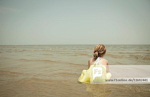 Mädchen spielt in Wellen am Strand