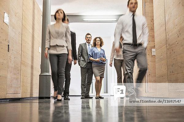 Geschäftsleute stehen im geschäftigen Flur