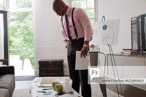 Mittlerer erwachsener Büroangestellter beim Betrachten von Plänen