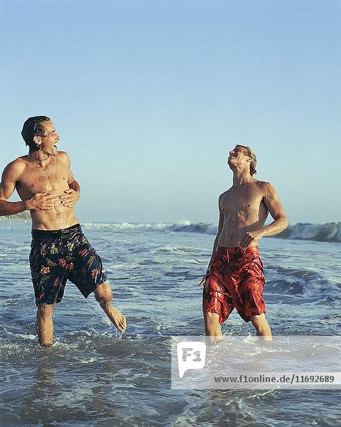 Männer spielen in Wellen am Strand