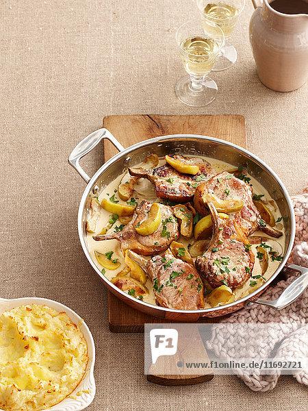 Gericht aus Schweinekoteletts und Äpfeln