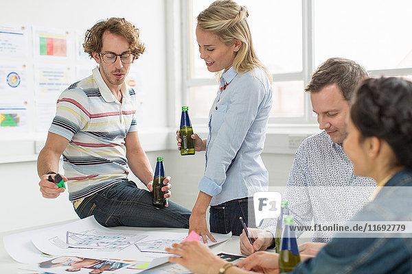 Bürokollegen besprechen kreative Pläne auf dem Schreibtisch