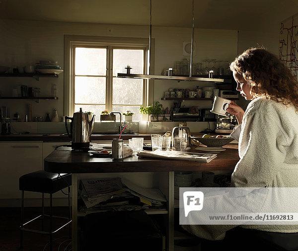 Junge Frau liest Zeitung am Küchentisch beim Frühstück