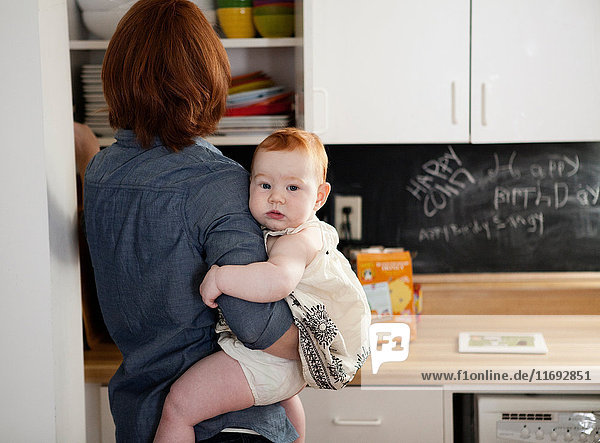 Mother holding baby daughter in kitchen