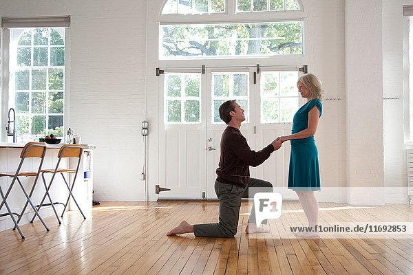 Couple in dance studio,  man on one knee