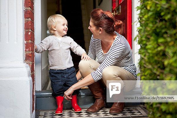 Kleiner Junge lächelt  nachdem seine Mutter ihm geholfen hat  Gummistiefel anzuziehen.
