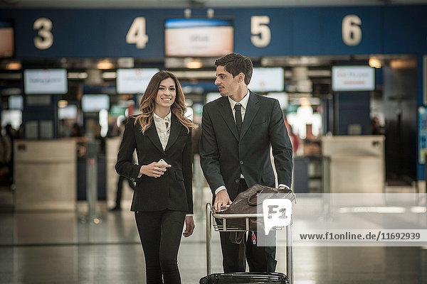 Geschäftsleute am Flughafen mit Gepäckwagen