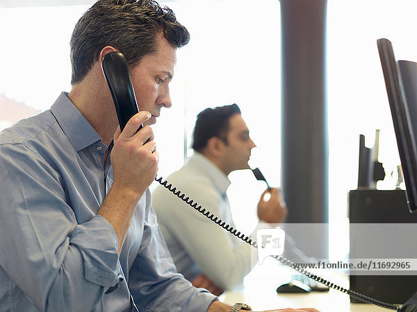 Geschäftsmann telefoniert am Schreibtisch
