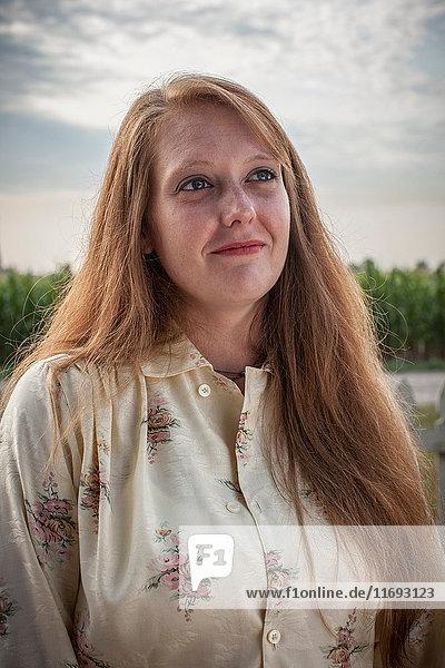 Frau mit langen roten Haaren im Feld