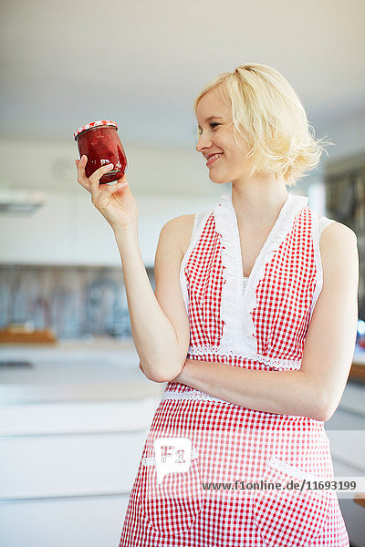 Frau hält einen Krug mit Gelee in der Küche
