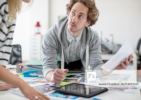 Junger Mann benutzt digitales Tablett und hält Papier im Kreativbüro
