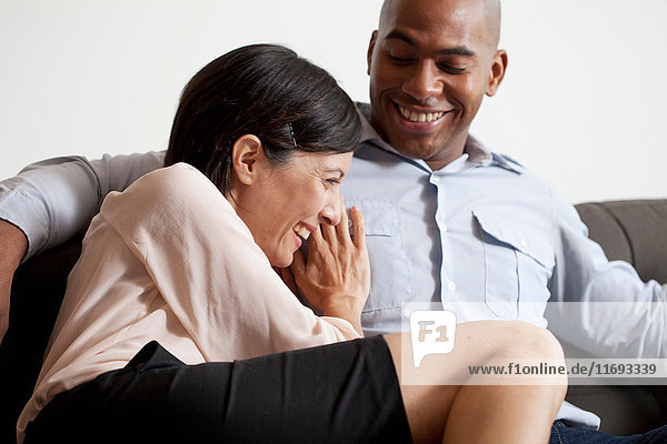 Couple relaxing on sofa  smiling