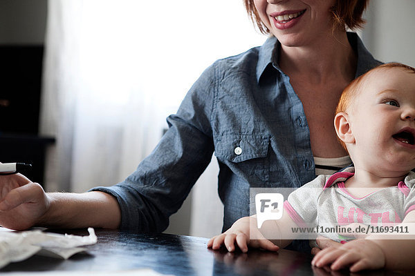Mutter schreibt mit kleiner Tochter auf dem Schoß