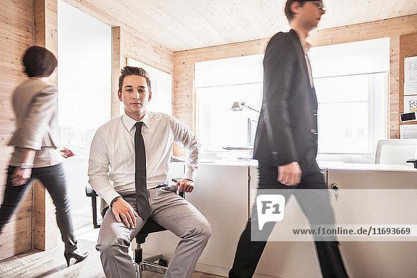 Geschäftsmann sitzt im geschäftigen Büro