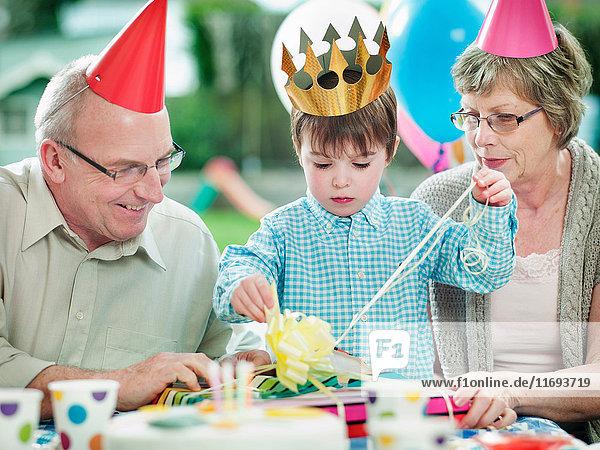 Junge mit Großeltern auf Geburtstagsfeier