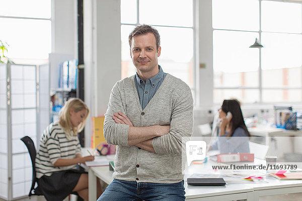 Reifer Mann sitzt auf dem Schreibtisch und lächelt im kreativen Büro  Porträt