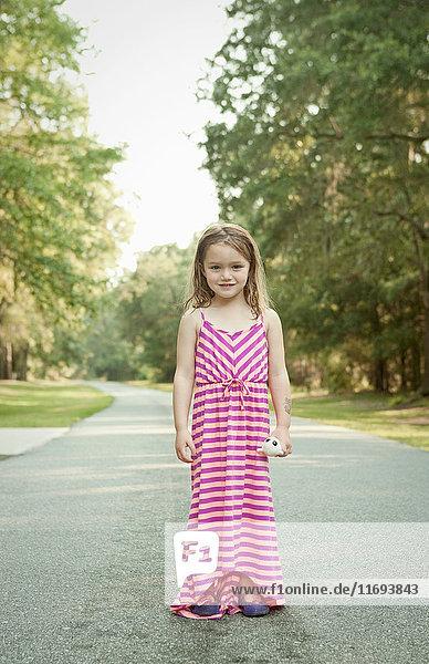 Lächelndes Mädchen steht auf ländlicher Straße
