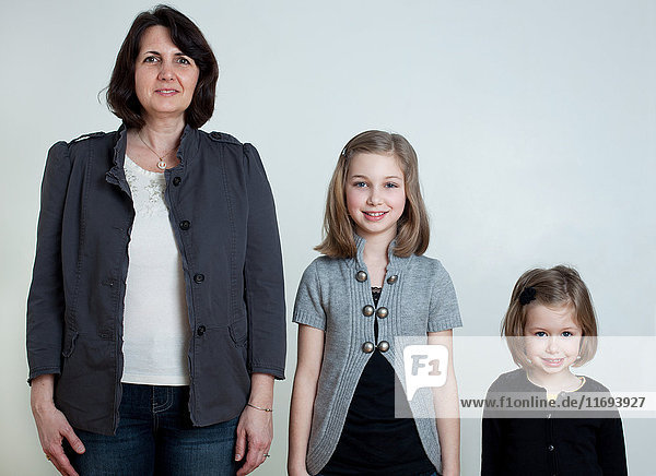Mother and two daughters standing together  portrait