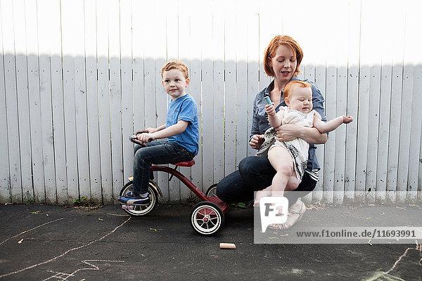 Mutter spielt im Hof mit zwei Kindern