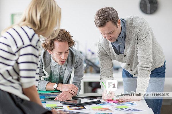Reifer Mann macht Notizen auf dem Schreibtisch bei Treffen mit Kollegen im Kreativbüro