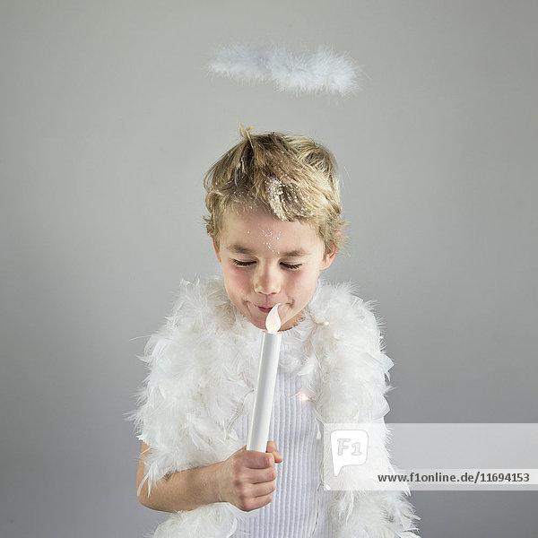 Junge mit Heiligenschein hält Kerze im Haus