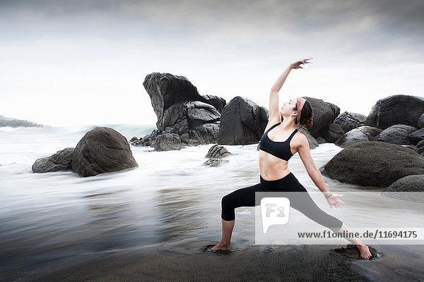 Woman practicing yoga on sandy beach