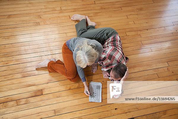 Couple doing crossword on wooden floor