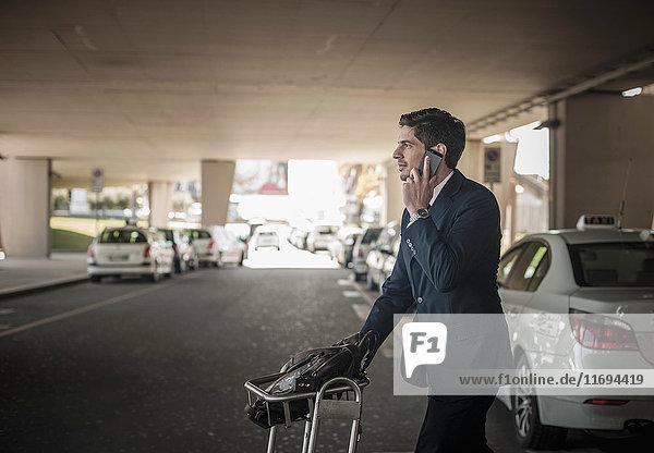 Junger Mann am Handy mit Gepäckwagen im Flughafen