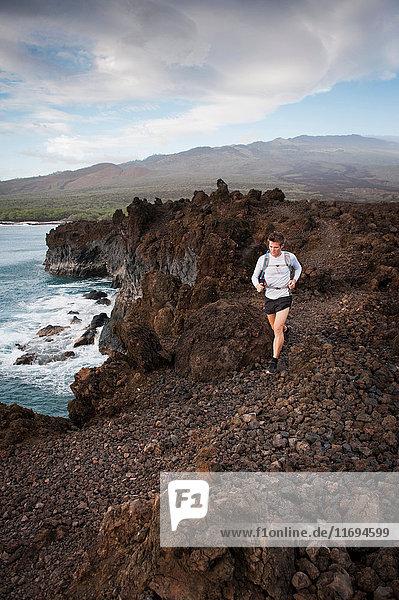 Mann rennt auf felsigem Landweg