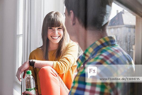 Lächelndes Paar spricht am Fenster