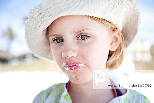 Kleines Mädchen mit Eiscreme um den Mund