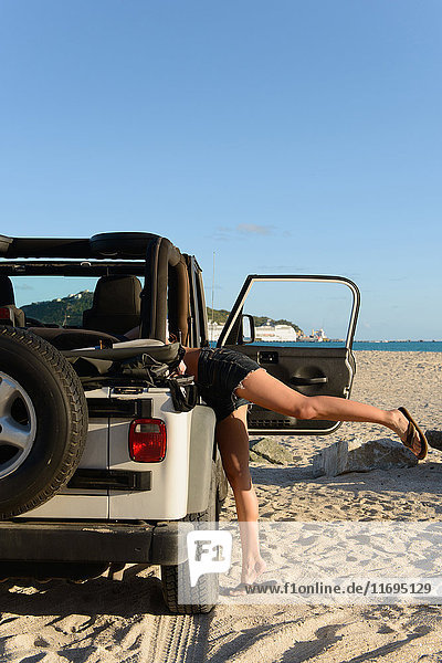Woman searching in jeep on beach