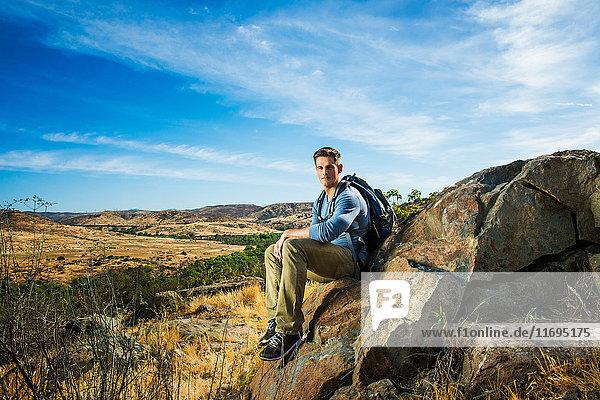 Male hiker sitting on rock