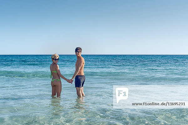 Couple standing in ocean together